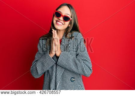 Young brunette woman wearing fashion and modern look praying with hands together asking for forgiveness smiling confident.