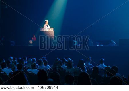 Silhouettes of anonymous people sitting in dark auditorium and listening to speaker talking from stage during business seminar