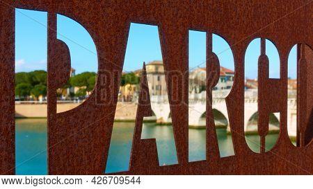 Rimini, Italy - February 25, 2020:  Bridge of Tiberius through the sign of 25th April public park in Rimini , Emilia-Romagna