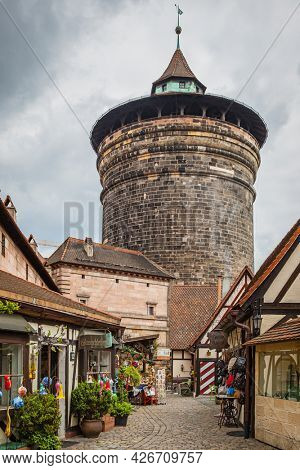 Nuremberg, Germany - May 17, 2016:  Small touristic market by medieval tower in the old town of Nuremberg