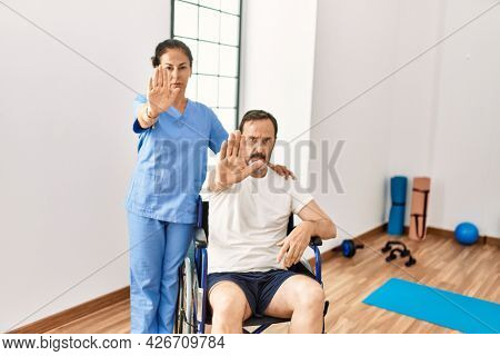 Hispanic middle age man sitting on wheelchair and nurse at rehabilitation clinic with open hand doing stop sign with serious and confident expression, defense gesture