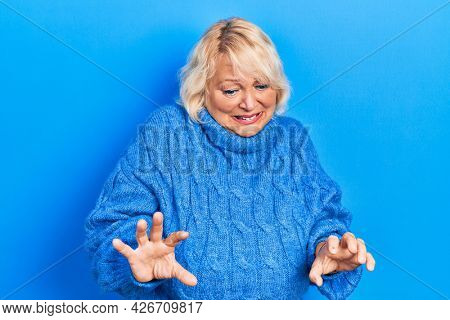 Middle age blonde woman wearing casual clothes disgusted expression, displeased and fearful doing disgust face because aversion reaction.