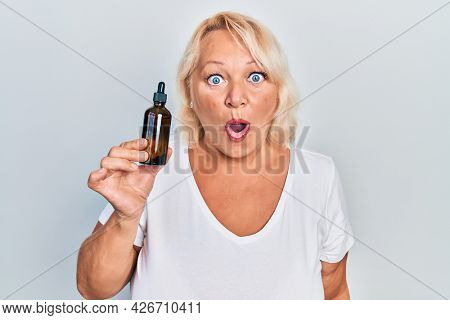 Middle age blonde woman using night serum scared and amazed with open mouth for surprise, disbelief face