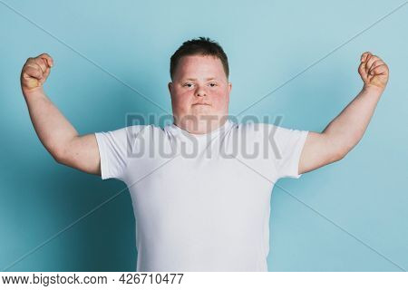 Proud boy with down syndrome flexing his arms