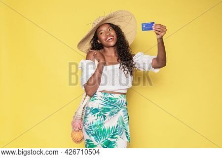 Tanned woman enjoying her summer vacation using a credit card