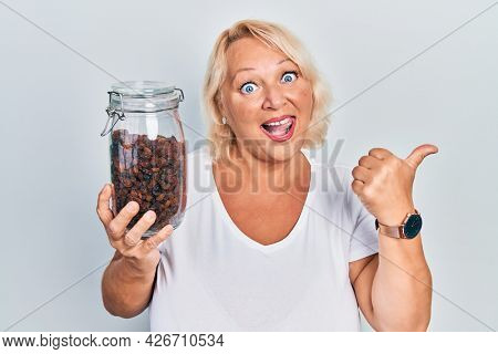 Middle age blonde woman holding raisins bowl pointing thumb up to the side smiling happy with open mouth