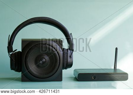 Wireless Headphones And A Square Black Audio Speaker Next To A Wi-fi Router Or Mini-computer In The