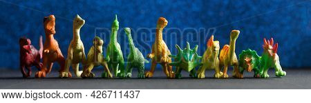 Many Colorful Toy Dinosaurs On A Dark Blue Background That Simulates The Night Sky. Material For Tea
