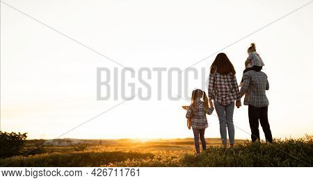 Happy Family Dad Mom And Daughters Walking On The Field Stand Admiring The Sunset Looking At The Sky