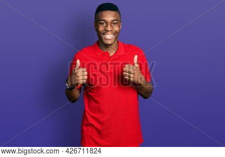 Young african american man wearing casual red t shirt success sign doing positive gesture with hand, thumbs up smiling and happy. cheerful expression and winner gesture.