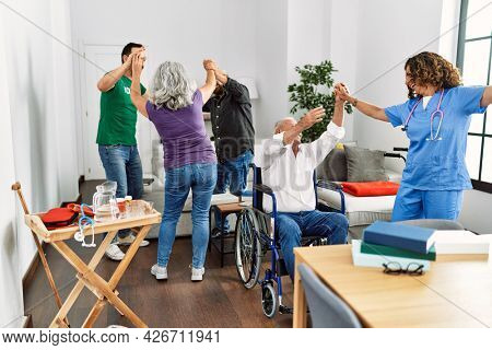 Group of retired people having party dancing with doctor and volunteer at nurse home.