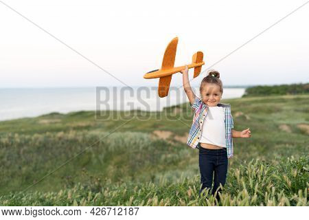 Charming Caucasian Girl Walks In The Summer In A Green Field Launches An Airplane Into The Sky And D