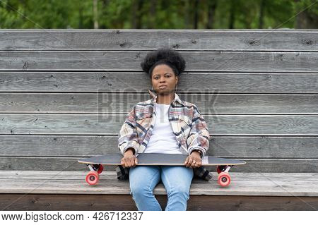 Upset African Woman Tired Or Depressed Sit In Apathy Outdoors On Wooden Bench Holding Longboard On K