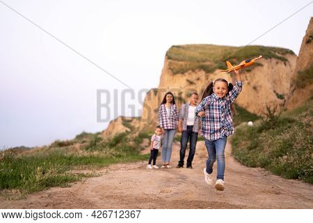 Foster Family Dad And Mom With Two Daughters Walking At Sunset Along A Cliff Or Rocks In The Summer