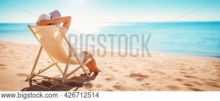 Woman In Stripes Sunhat Sitting On The Chaise On The Beach At The Sea Near Blue Water On Sunny Day.