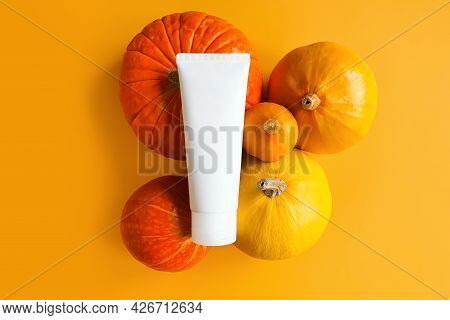 Unbranded White Squeeze Bottle Cosmetic Tube And Different Pumpkins A Lot Yellow Background.  Mockup