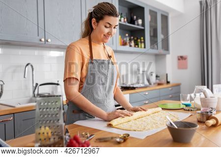 culinary, cooking food and people concept - happy smiling young woman rolling dough and baking roll buns on kitchen at home