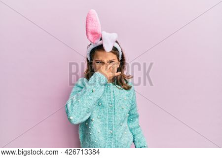 Little beautiful girl wearing cute easter bunny ears smelling something stinky and disgusting, intolerable smell, holding breath with fingers on nose. bad smell