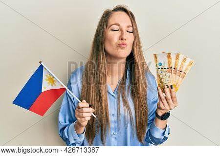 Young blonde woman holding philippine flag and philippines pesos banknotes looking at the camera blowing a kiss being lovely and sexy. love expression.