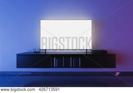 Front View Of A White Backlit Television Mockup In A Living Room With Blue And Red Lighting. 3d Rend