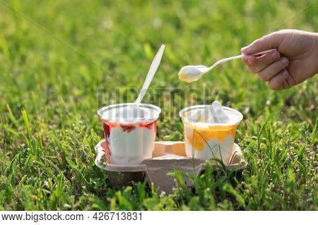Two Cups Of Ice Cream And Fruit Filling Stand On The Green Grass Of The Lawn. A Childs Hand With A S
