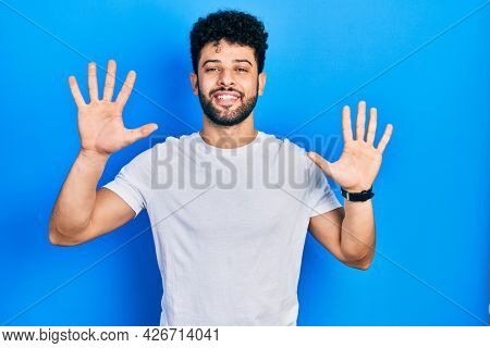 Young arab man with beard wearing casual white t shirt showing and pointing up with fingers number ten while smiling confident and happy.
