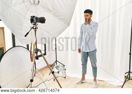 Arab young man posing as model at photography studio looking fascinated with disbelief, surprise and amazed expression with hands on chin