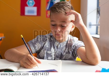 Caucasian schoolboy sitting at desk in classroom writing in book during lesson. childhood and education at elementary school.