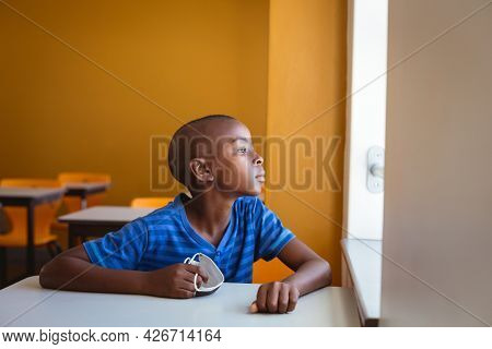 African american schoolboy holding face mask sitting at desk looking out of window in classroom. childhood and education at elementary school during coronavirus covid19 pandemic.