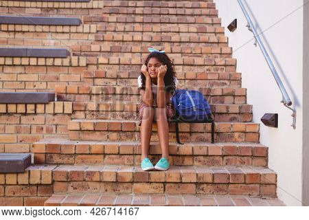 Bored african american schoolgirl sitting on steps in school yard with schoolbag. childhood and education at elementary school.