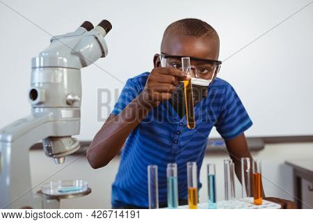 African american schoolboy in safety glasses and face mask looking at test tubes in science class. childhood and education at elementary school during coronavirus covid19 pandemic.