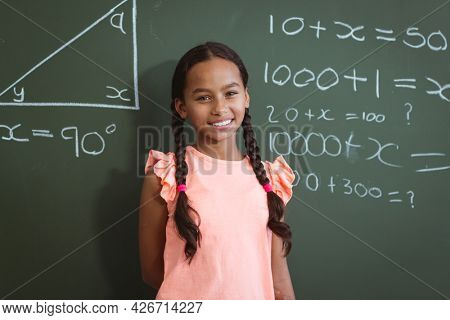 Portrait of smiling mixed race schoolgirl standing in front of chalkboard in classroom maths lesson. childhood and education at elementary school.