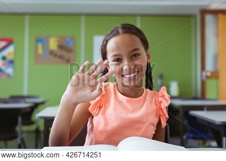 Portrait of smiling mixed race schoolgirl sitting at desk in classroom waving hand. childhood and education at elementary school.