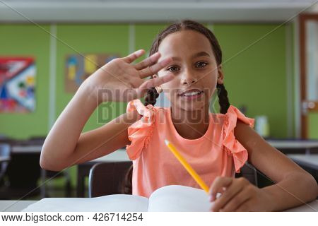 Portrait of smiling mixed race schoolgirl sitting at desk in classroom raising hand. childhood and education at elementary school.