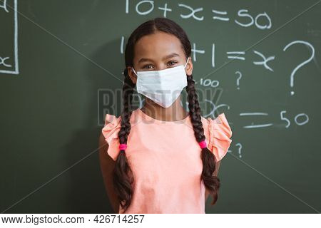 Portrait of mixed race schoolgirl in face mask standing in front of chalkboard in maths classroom. childhood and education at elementary school during coronavirus covid19 pandemic. .