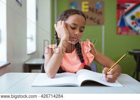 Mixed race schoolgirl in classroom sitting at desk concentrating and writing in book. childhood and education at elementary school.
