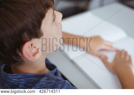 Blind caucasian schoolboy sitting at desk reading braille book with fingers. childhood and education at elementary school.