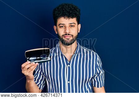 Young arab man with beard holding glasses in eyewear case thinking attitude and sober expression looking self confident