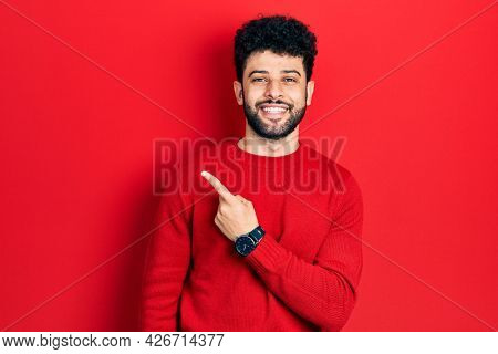 Young arab man with beard wearing casual red sweater cheerful with a smile of face pointing with hand and finger up to the side with happy and natural expression on face