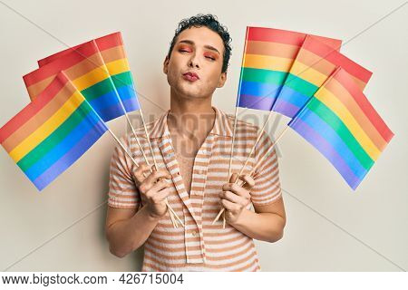 Handsome man wearing make up holding rainbow lgbtq flags looking at the camera blowing a kiss being lovely and sexy. love expression.