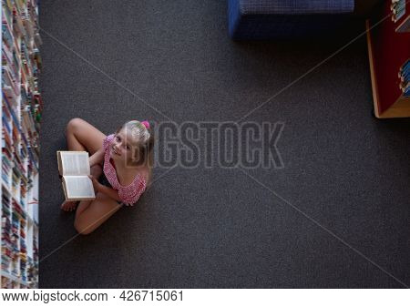 Overhead view of smiling caucasian schoolgirl sitting on floor reading book in school library. childhood and education at elementary school.