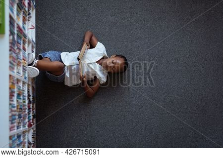 Overhead view of african american schoolgirl lying on floor reading book in school library. childhood and education at elementary school.