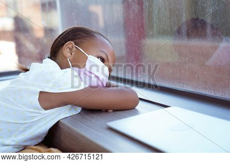 African american schoolgirl wearing face mask sitting in school classroom looking out of window. childhood and education at elementary school during coronavirus covid19 pandemic. .