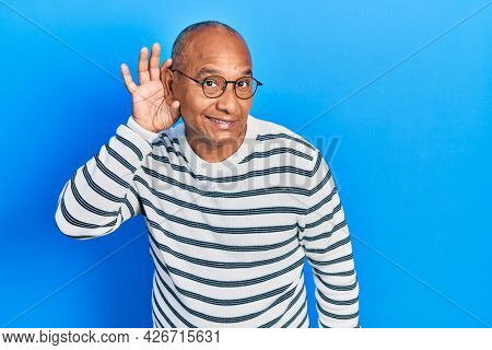 Middle age latin man wearing casual clothes and glasses smiling with hand over ear listening an hearing to rumor or gossip. deafness concept.