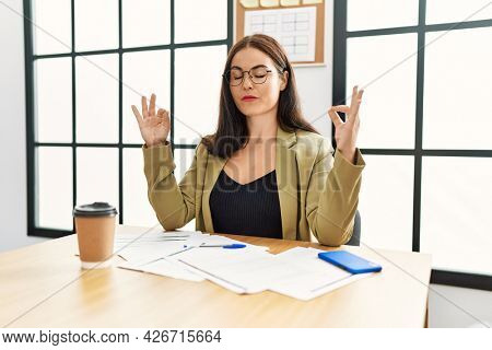 Young brunette woman wearing business style sitting on desk at office relax and smiling with eyes closed doing meditation gesture with fingers. yoga concept.