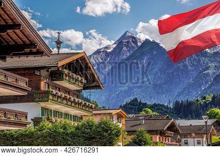 Kaprun Village With Hotel Against Kitzsteinhorn Glacier And Austrian Flag In Salzburg Region, Austri