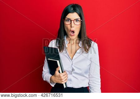 Young hispanic woman wearing business style holding computer laptop scared and amazed with open mouth for surprise, disbelief face