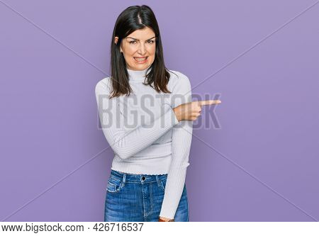 Beautiful brunette woman wearing casual clothes pointing aside worried and nervous with forefinger, concerned and surprised expression