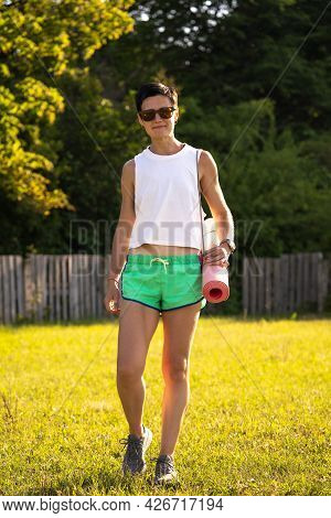 Young Beautiful Woman With Yoga Mat In A Park, Short Black Hair, Sunglasses And Shorts, Sport Outdoo
