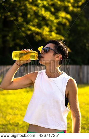 Young Beautiful Woman Drink Water From The Plastic Bottle In A Park After Training, Short Black Hair